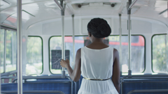 Woman  takes seat at the back of a bus and looks out window