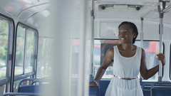 Woman standing on bus looking out window