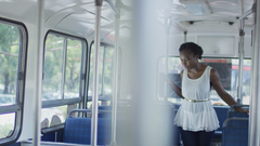 Woman standing on bus looking down then at camera