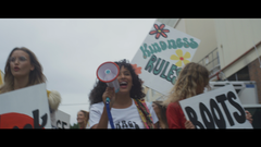 Women Walking Outisde With Signs And Megaphone