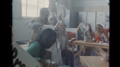 Group of women in a room shaking papers