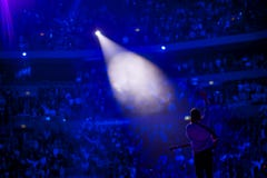 Spotlight on male singer on stage with guitar