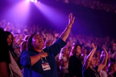 People praising and worshipping with hands on hearts