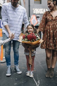Little girl holding flowers with family