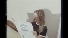 A young woman reading a newspaper