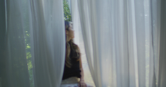 Woman Sitting at Window with Flowing Curtains