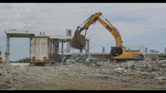 Excavator clearing rubble into truck from demolition site