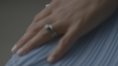 Womans hand with rings resting on blue fabric